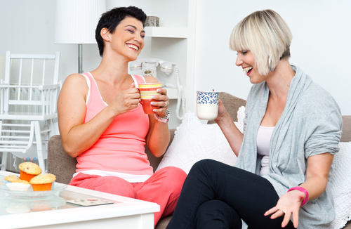 two happy woman friends chatting and smiling over coffee and cakes
